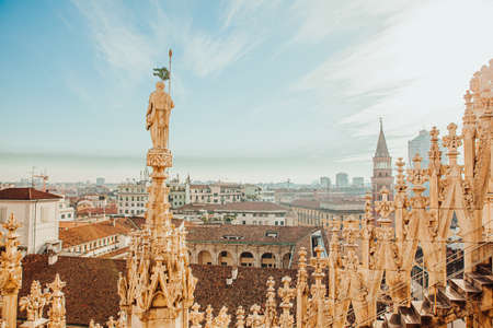 Roof of Milan Cathedral Duomo di Milano with Gothic spires and white marble statues. Top tourist attraction on piazza in Milan, Lombardia, Italy. Wide angle view of old Gothic architecture and art Stock fotó