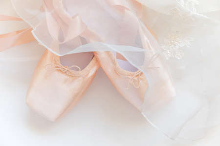 New pastel beige ballet shoes with satin ribbon and tutut skirt isolated on white background. Ballerina classical pointe shoes for dance training. Ballet school concept. Top view flat lay copy space