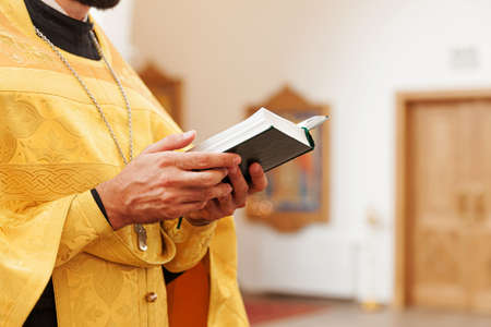Orthodox Church. Christianity. Priest hands holding Holy Bible book in traditional Orthodox Church background on wedding day Easter Eve or Christmas celebration. Religion faith pray symbol