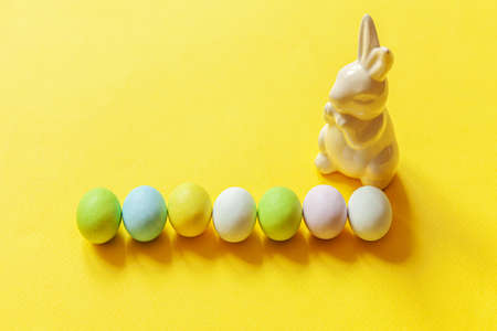 Happy Easter concept. Preparation for holiday. Easter candy chocolate eggs sweets and bunny toy isolated on trendy yellow background. Simple minimalism copy space