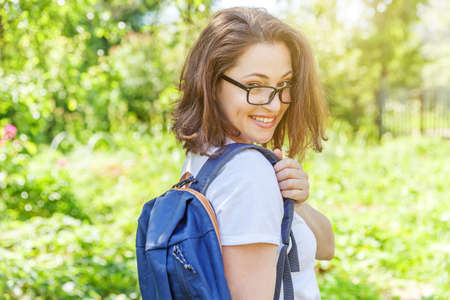 Happy beautiful positive student girl in eyeglasses with backpack smiling on green park background. Woman having rest in campus during lunch break. Education and leisure concept Reklamní fotografie