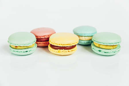 Sweet almond colorful pastel pink blue yellow green macaron or macaroon dessert cake isolated on white background. French sweet cookie. Minimal food bakery concept. Copy space Reklamní fotografie
