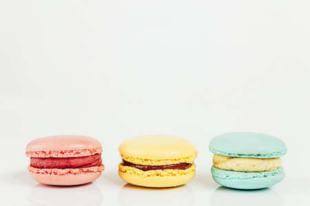 Sweet almond colorful pastel pink blue yellow macaron or macaroon dessert cake isolated on white background. French sweet cookie. Minimal food bakery concept. Copy space