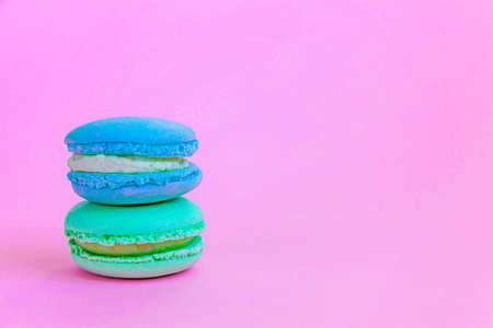 Sweet almond colorful unicorn blue green macaron or macaroon dessert cake isolated on trendy pink pastel background. French sweet cookie. Minimal food bakery concept. Copy space