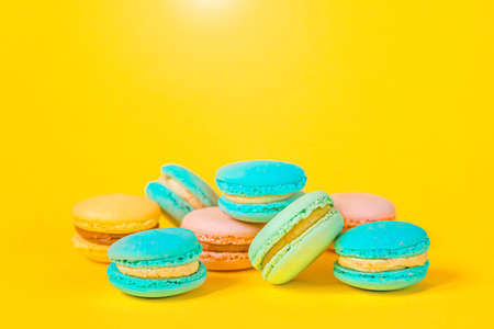 Sweet almond colorful unicorn pink blue yellow green macaron or macaroon dessert cake isolated on trendy yellow modern fashion background. French sweet cookie. Minimal food bakery concept. Copy space