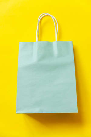 Simply minimal design shopping bag isolated on yellow background. Online or mall shopping shopaholic concept. Black friday Christmas season sale. Flat lay top view copy space mock up