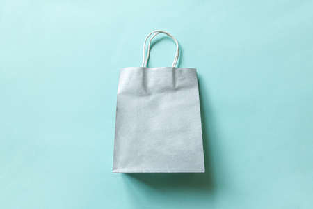 Simply minimal design shopping bag isolated on blue pastel background. Online or mall shopping shopaholic concept. Black friday Christmas season sale. Flat lay top view copy space mock up