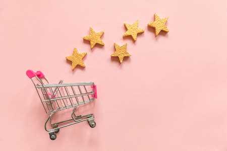 Simply flat lay design small supermarket grocery push cart for shopping and 5 gold stars rating isolated on pink pastel background. Retail consumer buying online assessment and review concept Reklamní fotografie
