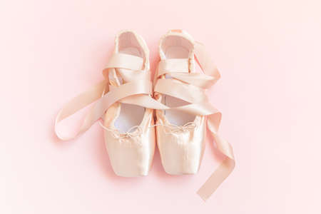 New pastel beige ballet shoes with satin ribbon isolated on pink background. Ballerina classical pointe shoes for dance training. Ballet school concept. Top view flat lay copy space