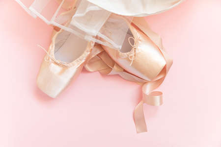 New pastel beige ballet shoes with satin ribbon and tutut skirt isolated on pink background. Ballerina classical pointe shoes for dance training. Ballet school concept. Top view flat lay copy space