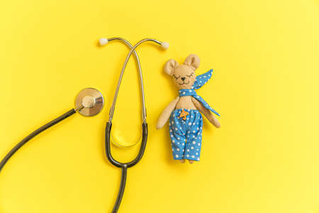 Simply minimal design toy bear and medicine equipment stethoscope isolated on yellow background. Health care children doctor concept. Pediatrician symbol. Flat lay top view layout copy space