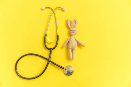 Simply minimal design toy bunny and medicine equipment stethoscope isolated on yellow background. Health care children doctor concept. Pediatrician symbol. Flat lay top view layout copy space