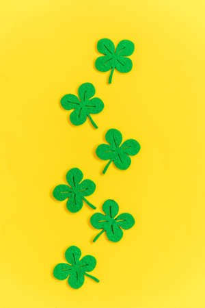 St Patricks Day background. Simply minimal design with green shamrock. Clover leaves isolated on yellow background. Symbol of Ireland. Lucky fortune wish concept. Flat lay top view layout copy space Reklamní fotografie