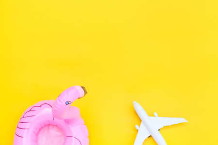 Summer beach composition. Minimal simple flat lay with plane and Inflatable flamingo isolated on yellow background. Vacation travel adventure trip concept. Top view copy space