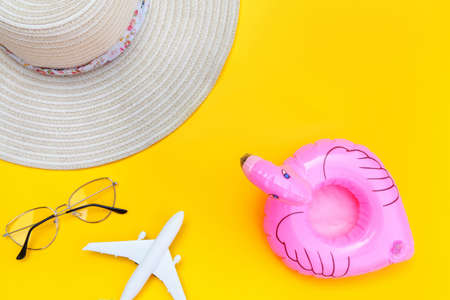 Summer beach composition. Minimal simple flat lay with plane sunglasses hat and Inflatable flamingo isolated on yellow background. Vacation travel adventure trip concept. Top view copy space Reklamní fotografie