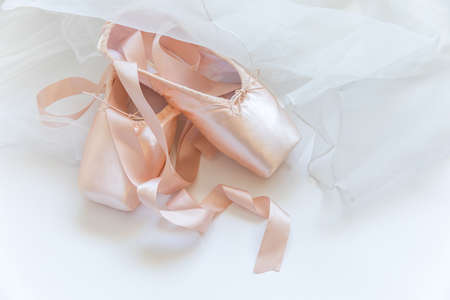 New pastel beige ballet shoes with satin ribbon and tutut skirt isolated on white background. Ballerina classical pointe shoes for dance training. Ballet school concept. Top view flat lay copy space Reklamní fotografie