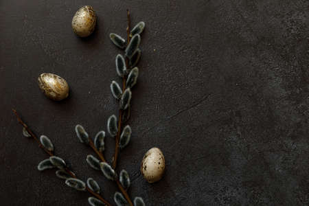Happy Easter concept. Preparation for holiday. Golden decorated easter eggs willow on trendy grunge scratched dark black shale background. Simple minimalism flat lay top view copy space