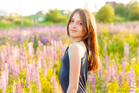Happy teenage girl smiling outdoor. Beautiful young teen woman resting on summer field with blooming wild flowers green background. Free happy kid teenager girl, childhood concept