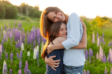 Young mother embracing her child outdoor. Woman and teenage girl on summer field with blooming wild flowers green background. Happy family mom and daughter playing on meadow 스톡 콘텐츠