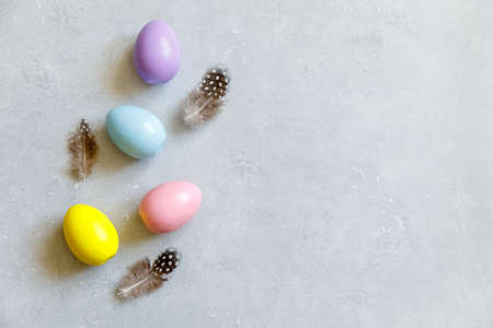 Happy Easter concept. Preparation for holiday. Colorful decorated easter eggs feather on concrete stone grey background. Simple minimalism flat lay top view copy space 스톡 콘텐츠