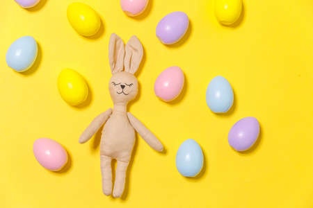 Happy Easter concept. Preparation for holiday. Colorful decorated easter eggs and bunny toy isolated on trendy yellow background. Simple minimalism flat lay top view copy space 스톡 콘텐츠