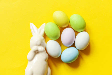 Happy Easter concept. Preparation for holiday. Easter candy chocolate eggs sweets and bunny toy isolated on trendy yellow background. Simple minimalism flat lay top view copy space