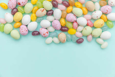 Happy Easter concept. Preparation for holiday. Easter candy chocolate eggs and jellybean sweets isolated on trendy pastel blue background. Simple minimalism flat lay top view copy space