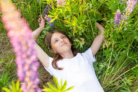 Happy teenage girl smiling outdoor. Beautiful young teen woman resting lying on summer field with blooming wild flowers green background. Free happy kid relaxing and enjoying nature 스톡 콘텐츠 - 165092482