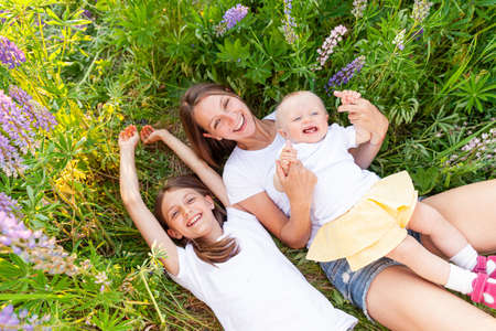 Young mother embracing her kids outdoor. Woman baby child and teenage girl lying down on summer field with blooming wild flowers green background. Happy family mom and daughters playing on meadow