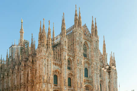 Famous church Milan Cathedral Duomo di Milano with Gothic spires and white marble statues. Top tourist attraction on piazza in Milan Lombardia Italy Wide angle view of old Gothic architecture and art 스톡 콘텐츠