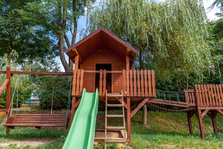 Empty modern wooden children playground set on green yard in public park in summer day. Funny toy land for kids. Urban exercise activities for child outdoors. Neighborhood childhood concept 스톡 콘텐츠