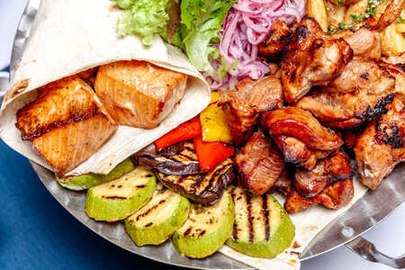 Mixed grill meat fried vegetables and grilled salmon fish fillets decoration in warm dish. Assorted delicious grilled kebab served with herbs on platter. Restaurant menu barbecue plate. Bbq party meal