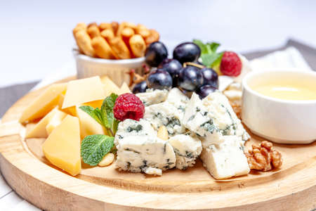 Board with different types of cheese. Cheeses mix set dor blu chedar parmesan brie honey sauce finger bread and grape on wooren palte. Restaurant menu breakfast plate. Healthy snack assortment