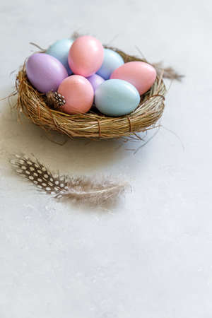 Happy Easter concept. Preparation for holiday. Colorful decorated easter eggs in nest with feather on concrete stone grey background. Simple minimalism flat lay top view copy space 스톡 콘텐츠