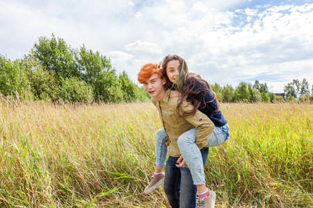 Summer holidays vacation happy people concept. Loving couple having fun in nature outdoors. Happy young man piggybacking his girlfriend. Happy loving couple embracing outdoor at summertime