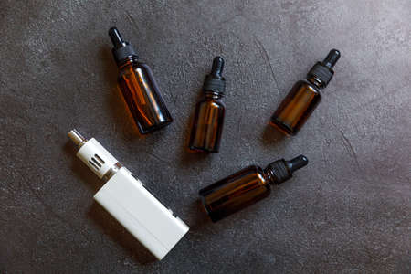 Vaping device e-cigarette electronic cigarette and liquid bottles on dark black stone shale background. Vape device for alternative smoking. Vaping shop concept. Gadget for vaper. Vaping accessories