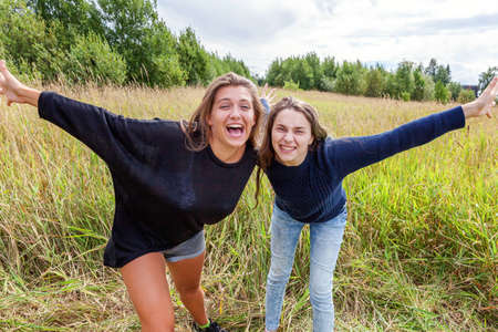 Summer holidays vacation happy people concept. Group of two girl friends sisters dancing hugging and having fun together in nature outdoors. Lovely moments best friend Reklamní fotografie