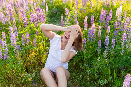 Happy girl smiling outdoor. Beautiful young brunete woman resting on summer field with blooming wild flowers green background. Free happy european woman. Positive human emotion facial expression 스톡 콘텐츠