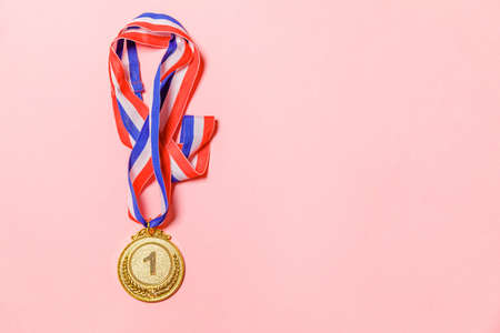 Simply flat lay design winner or champion gold trophy medal isolated on pink colorful background. Victory first place of competition. Winning or success concept. Top view copy space 스톡 콘텐츠