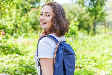 Happy positive student girl with backpack smiling on green park background. Woman having rest in campus during lunch break. Education and leisure concept
