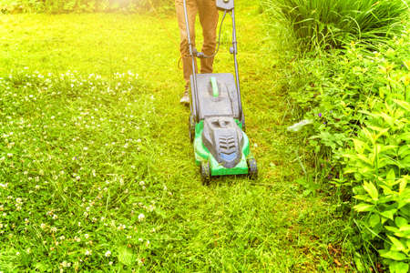 Man cutting green grass with lawn mower in backyard. Gardening country lifestyle background. Beautiful view on fresh green grass lawn in sunlight, garden landscape in spring or summer season
