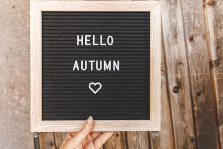 Autumnal Background. Woman hand holding black letter board with text phrase Hello Autumn on wooden palnks backdrop. Thanksgiving banner. Hygge mood cold weather concept