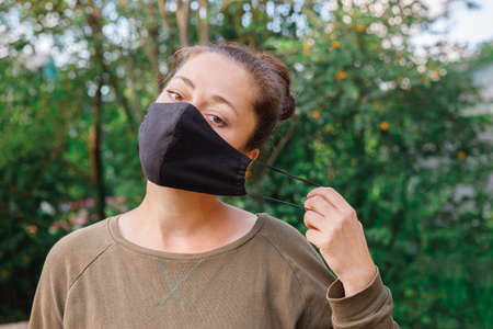 Happy positive girl takes off protective medical mask from face outdoors. Young woman removing mask smiling after vaccination. 스톡 콘텐츠