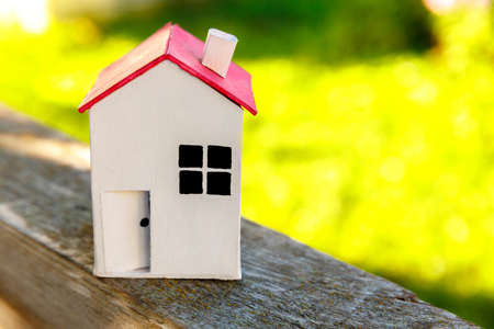 Miniature white toy model house in wooden background near green backdrop. Eco Village, abstract environmental background. Real estate mortgage property insurance dream home ecology concept 스톡 콘텐츠