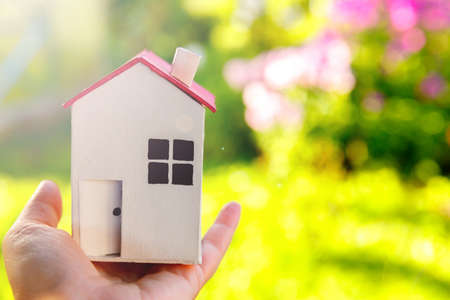 Miniature model house in female woman hand on green outdoor background. Eco Village, abstract environmental background. Real estate mortgage property insurance dream home ecology concept