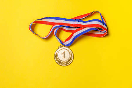 Simply flat lay design winner or champion gold trophy medal isolated on yellow colorful background. Victory first place of competition. Winning or success concept. Top view copy space