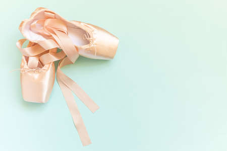 New pastel beige ballet shoes with satin ribbon isolated on blue background. Ballerina classical pointe shoes for dance training. Ballet school concept. Top view flat lay copy space