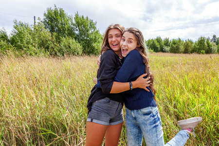 Summer holidays vacation happy people concept. Group of two girl friends sisters dancing hugging and having fun together in nature outdoors. Lovely moments best friend 스톡 콘텐츠