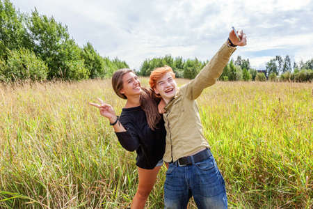 Summer holidays vacation happy people concept. Loving couple having fun together in nature outdoors. Happy young man taking making romantic selfie with girlfriend. Happy loving couple at summertime 스톡 콘텐츠
