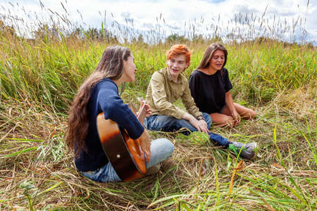 Summer holidays vacation music happy people concept. Group of three friends boy and two girls with guitar singing song having fun together outdoors. Picnic with friends on road trip in nature